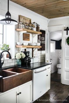This farmhouse kitchen is decorated for spring and summer - love the wood ceiling, copper sink, barn door, shiplap and open shelving