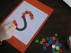Building literacy skills: children use buttons to trace letters to help build familiarity with the letter and pracice word recognition skills. Parents-- don't forget to communicate the letter and words that begin with that letter!