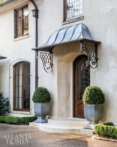 Though the home was less than 10 years old when the Bromenschenkels moved in, they were drawn to how Summerour used materials that made the home appear as if it had stood for decades. The stucco and limestone exterior, zinc pots and overhang and potted boxwoods reflect French Normandy style. French Provincial Home, Enchanted Home, Entry Gates, Front Entrances, Facade House, Front Door Decor, Beautiful Architecture, Front Entry, Front Doors