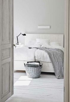 Classic bedroom, white, grey, bed, white sheets, wicker basket, grey wall, throw.
