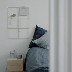 Serene blue bedroom with linen sheets in Stockholm, Sweden. Grid by wallment design, made in Finland.