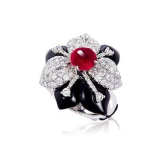 A RUBY, ONYX AND DIAMOND FLOWER RINg. Set with a cabochon ruby to the brilliant-cut diamond and carved onyx undulating petals, further enhanced by the diamond-set and carved onyx foliate motifs on the ring hoop, mounted in 18k white gold, ring size 6 1/2.