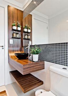 bancada curva em madeira banheiro com painel e prateleiras na lateral, prateleira inferior, cuba de apoio torneira de mesa na lateral