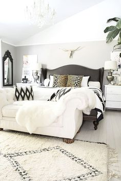 neutral black and white bedroom with brass and leopard accents, Beni Ourain rug, fur, leather studded wingback bed, button tufted chaise/end of the bed bench- Cuckoo4Design