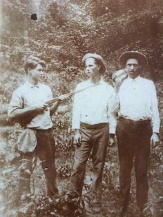 Photos of Past Appalachian Life | Three 14 Mile Creek men pose with a rifle and jar of moonshine, 1930s