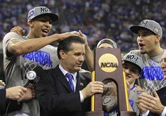 Kentucky Wildcats forward Anthony Davis (L) messes up the hair of head coach John Calipari as he holds the championship trophy after the Wildcats defeated the Kansas Jayhawks in the men's NCAA Final Four championship college basketball game in New Orleans, Louisiana, April 2, 2012.