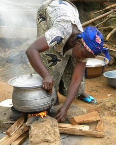Hard working sister cooking fish and rice for the brothers and sisters at a Kingdom Hall build, Guinea, west Africa.
