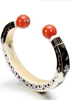 AN ART DECO IVORY, ENAMEL, CORAL, DIAMOND AND GOLD SUDANESE BANGLE, CARTIER, CIRCA 1920.
