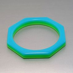 Here's a vibrant splash of color for your wrist. In a distinctive octagonal shape, this bangle bracelet is a laminate of aqua blue and lime ...