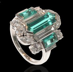 Unusual cocktail ring the central panel set with an elongated hexagonal emerald and two further step-cut emeralds highlighted by baguette, brilliant and marquise diamonds Art Deco circa 1930