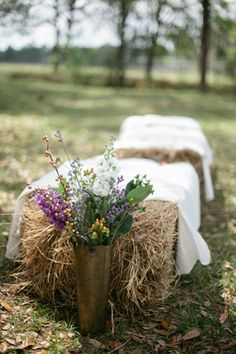 Straw bale pews with floral end pieces. {Photography: Dave Lapham « Southern Weddings}