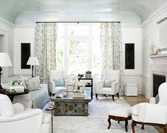 Traditional living room in pale blue and white.  Curved ceilings painted in high gloss glossy light pale blue.  Ceilings look like they have a coat of lacquer on them!  Classic white wingback armchairs chairs work in this space too.  Not my style but I like the chintz drapes.  Designed by Beth Webb interior design. http://cococozy.com