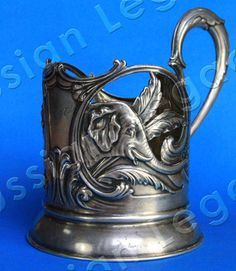 A Podstakannik (Russian Tea Glass Holder)  Authentic Soviet silver 875 podstakannik or tea glass holder by the Moscow jewelry factory Extremely rare collectible Elephants are featured on the sides Ships within 3 business days Etched crystal glass holder insert is included free of charge