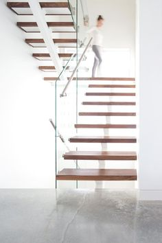 These modern stairs feature walnut treads, while brushed stainless steel handrails are attached to glass balustrades to complete the staircase.