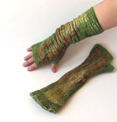Warm and soft mitts is felted from merino wool. Felted mittens are decorated with viscose fibers, fancy yarn, silk fabric Warm yourself or your