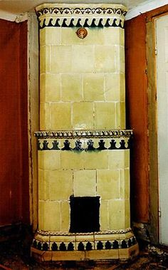Yellow-green stove with a mantle, from ca 1830. Decorations in blue and brown. Height 245 cm.