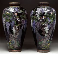 PAIR OF CLOISONNE VASES. Meiji period, Japan. Decoration of flocks of finches in wisteria with other flowers in silver wire on a midnight blue ground. Hayashi school mark. Size: 18″h