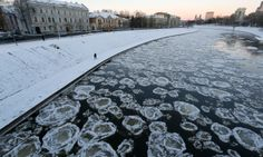 It's a cold winter day in  Vilnius, Lithuania as a pedestrian walks along the banks of the Neris river as temperatures dipped to -18 degrees celsius.