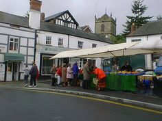 The market on High Street,  In Church Stretton, England which has been held in the town since 1214; in the background is the tower of St Laurence's Church