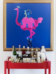 Bold peacock and monkey art above a lacquered red bar cart // bars