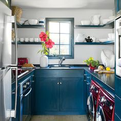 Deep blue-painted cabinets and shelves in the small galley kitchen give the room elements of depth and drama.