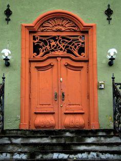 Orange doors on green building