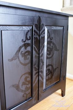 Black on black.Wood cabinet painted with large damask pattern.