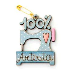 Botón decorativo de madera en azul con forma de máquina de coser y 100% artista.  Medida: 3.6 x 5.5 cm.