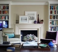 Avoid placing like items at opposite ends of a fireplace mantel. (Imagine how dull this mantel would have been if one candlestick sat on each end.) Instead, rely on clusters of objects to balance one another. Propped and overlapped photographs feel more casual and curated than art that's hung, and in this instance help unite the vignettes on either end of the mantel.