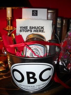 """Mother Shucker's """"ShuckIt Bucket""""  It comes filled with everything you need to attend your next oyster roast – a handpainted oyster knife, matching towel, matching drink holder and, of course, a jar of Mother Shucker's Original Cocktail Sauce. Stop by the Oyster Bar Columbia today to get yours!"""