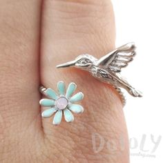 - Description - Sizing A wrap around ring made with a realistic hummingbird on one end in silver and a blue flower on the other! It looks like a hummingbird is hovering over the flower on your ring! D