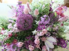 Bouquet of early summer country garden flowers in blue and pink. - aquilegia, allium, polygonum and hespiris