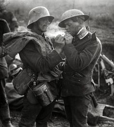 German soldier giving wounded British soldier a light, c.1918. There was never a good war, or a bad peace : Photo