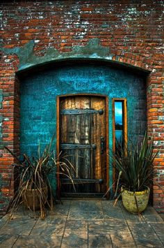 awesome front door Love the roughness and the hardware. Gorgeous turquoise colors work so well with the bricks and hardware.