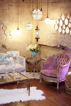 Beautiful decor using purple, gold, aqua, and white.  The exposed stone wall amd velvet furniture create a nice juxtaposition between hard and soft elements in this room.  The light purple velvet button tufted chair and the soft white sofa contrast nicely with the room's harder elements.  The hanging lights give off an overall soft glow.