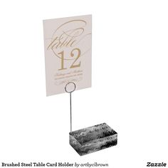 """The perfect complement to your table cards, this high quality, artist designed table card holder is sturdy and sleek. The Brushed Steel Table Card Holder designed by Artist C.L. Brown features an abstract kinetic light painting edited for design in contemporary shades of steel grey, ivory white, and coal black that you'll love. This high quality acrylic base with stainless steel metal card holder is perfect for your wedding or special event. Dimensions: 1.75""""l x 3""""w x 1""""h (Acrylic base); 5""""h…"""