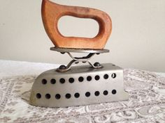 Originates from around the 1940s-'50s.  It's actually a paraffin iron with wood handle. These existed in the UK up until the sixties.  As a curiosity item, you can put a tea light inside the iron to glow through the holes.
