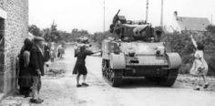 Civils acclamant le passage d'un char Stuart dans un village près de La Haye-du-Puits. Deux femmes jettent des fleurs, juillet 1944