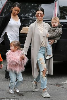 Got her hands full: The reality star carried son Reign, one, while six-year-old Mason and Penelope walked alongside