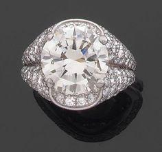 Bague en double jonc de platine pavé de diamants, centrée d'un diamant rond pesant environ 5 cts.