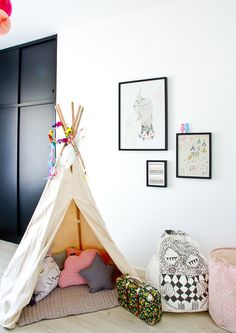 white and black childrens room with wigwam, beanbag and artwork