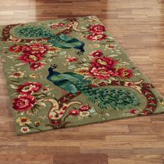 """The wool Peacock Flora Area Rugs feature pops of vibrant colors perfect for your room. Area rugs, .5"""" thick, have allover floral designs on a sage background accented with two brilliantly-colored peacocks. Peacock rug colors include eucalyptus, French blue, celestial blue, pale blue, aqua mist, dark gold, golden yellow, dark copper, crimson, cranberry, burgundy, ivory, cypress, and sage. We recommend professional cleaning by a rug cleaner. Made in China."""
