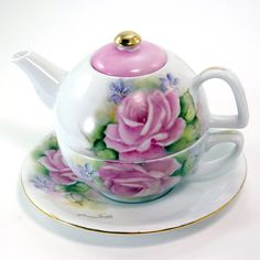 "Rosemary's Porcelain Art Hand Painted Unique Tea for One: This is a teapot, cup and saucer all in one.  Designed with tea roses and accented with dainty lavender violets, trimmed slightly with gold and enamel. Includes teapot, tea cup and saucer hand painted by Nebraska artist Rosemary Thomas of Rosemary's Porcelain Art located in Milford, NE. Signed by the artist. Priced as a set. Pot holds 16 oz. saucer 6 3/4"". Set is 6"" high. May be personalized. $64.95"