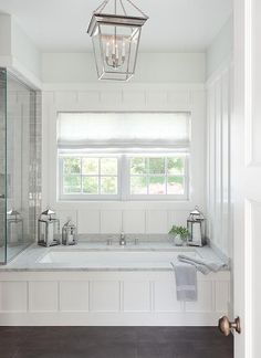 The perfect place to relax, this stunning cottage bathroom boasts a wainscoted drop in bathtub accented with a marble deck a polished nickel tub filler fixed in front of a board and batten wall framing a window dressed in a white linen shade lit by a Small Cornice Hanging Lantern.
