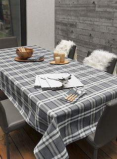 Gray wood accent wall and faux sheepskin throws over the chairs make for a cozy fall/winter dining space
