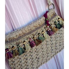 Bolso a crochet, adornado por borlas, todo en colores tierra.