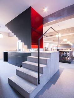 Immagine scala moderna, molto originale,  realizzata in due pezzi. La parte inferiore è creata in cemento ed è appoggiata sul pavimento e la parte superiore è realizzata in ferro, verniciato in rosso, ed è ancorata al soffitto - Idee scale moderne all'avanguardia.