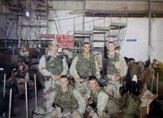 """Good, squatting front left, and Pfc. Todd Blackburn, (beside him) who was seriously wounded during one mission, is pictured with other members of their platoon, known as """"Chalks."""" Photo provided"""