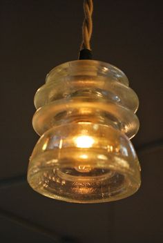 Repurposed Antique Insulator Pendant ----- We have several of these in our shop, both blue and clear; what a unique way to use them!