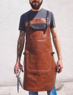 Unique universal handmade leather apron for Mens / Womens by Fashion Racing ✂️ The rugged leather shop apron, made from a single piece of high quality leather. . Great style with tough, trustworthy longevity.  This apron features brass buckles. The straps are all leather and the cross fastenings of the back straps are streamlined and comfortable. The apron Reinforced on the sides  The oily utility leather that I use gives the apron a rustic, old world look and has a forgiving quality tha...
